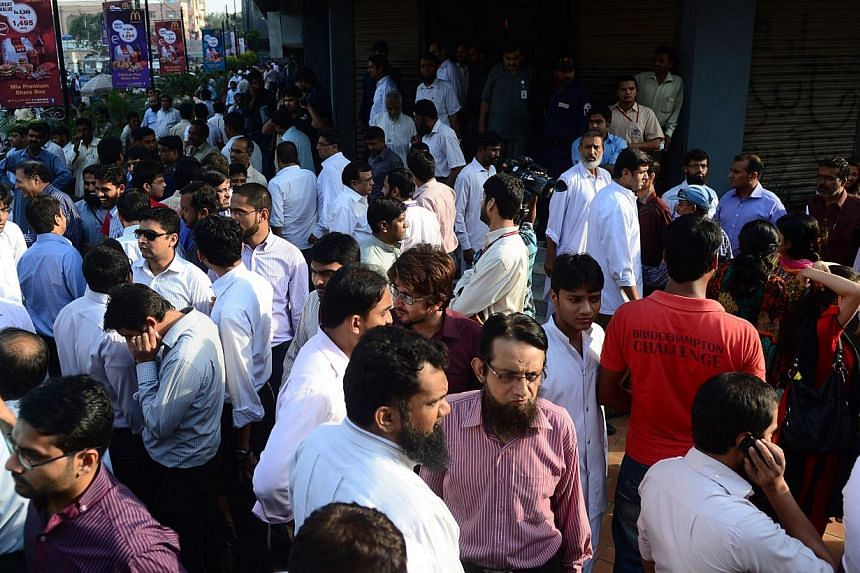 Pakistani pedestrians and office workers gather on a street after an earthquake in Karachi on Tuesday, Sept 24, 2013.Heavy casualties were feared on Tuesday after a 7.8-magnitude earthquake hit south-western Pakistan, demolishing houses and sen
