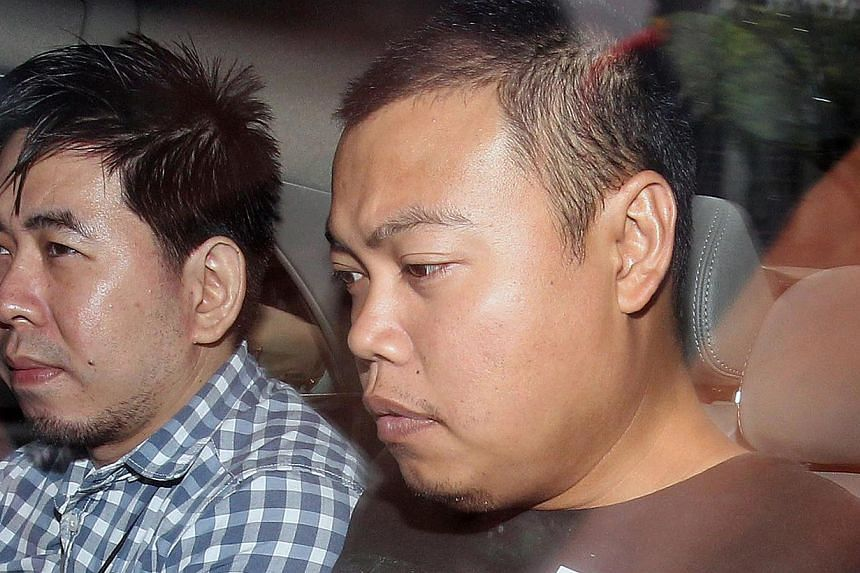 Kovan double murder suspect, Iskandar Rahmat (right), being brought to the Subordinate Court on July 15, 2013. The trial of a police officer charged with the double murder in Kovan is not expected to take place until next year. -- ST FILE PHOTO: