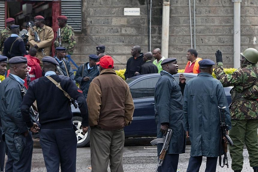 Kenyan police and army soldiers stand near the Westgate Mall in Nairobi, Kenya on Tuesday, Sept 24, 2013.A British security source said on Tuesday it was a possibility that the widow of a suicide bomber who attacked London in 2005 was involved