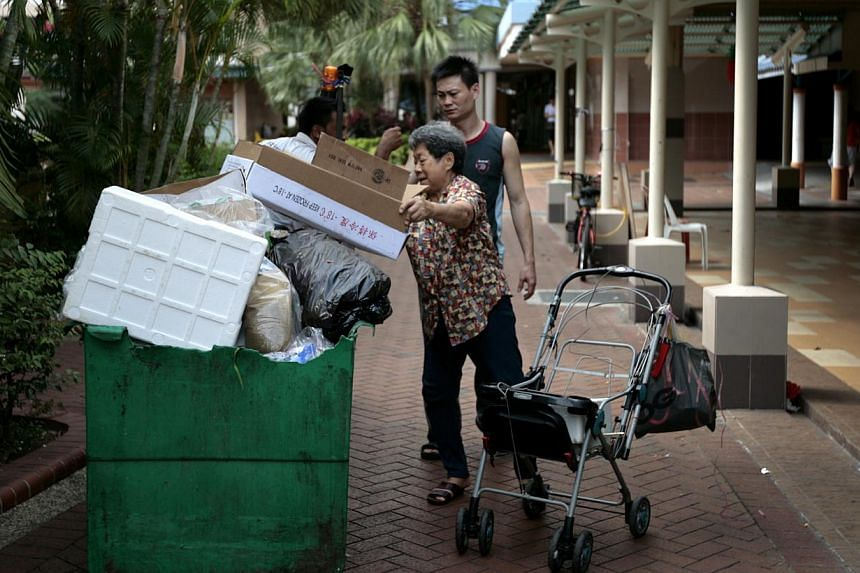 An elderly rag and bone woman picking up a cardboard box outside Geylang Bahru food centre. Speakers at a National University of Singapore (NUS) forum on Tuesday called for a better understanding of poverty here and more targeted measures to address