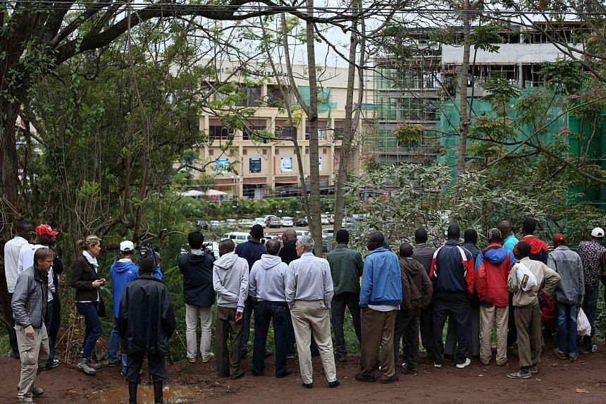 Residents look at the military rescue operation at the Westgate shopping centre in the capital Nairobi on Tuesday, Sept 24, 2013. One of the Islamist attackers besieging a Nairobi shopping mall handed chocolate to a four-year-old British boy caught u