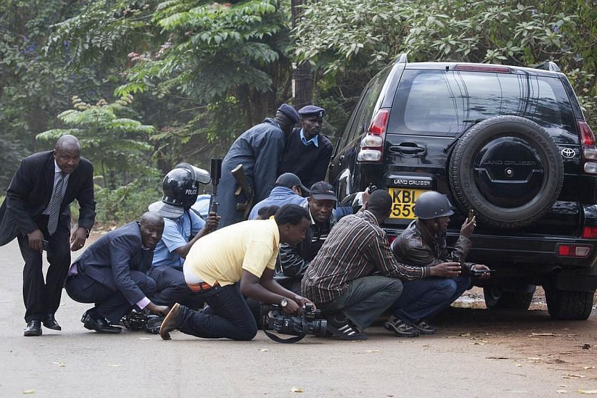 Police officers and members of the media take cover at a distance from the Westgate Shopping Centre after continuous gunfire was heard coming from the mall in Nairobi on Monday, Sept 23, 2013. -- PHOTO: REUTERS