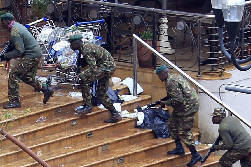 Kenya Defence Forces soldiers run to take their position at the Westgate shopping centre, on the fourth day since militants stormed into the mall, in Nairobi on Tuesday, Sept 24, 2013. -- PHOTO: REUTERS