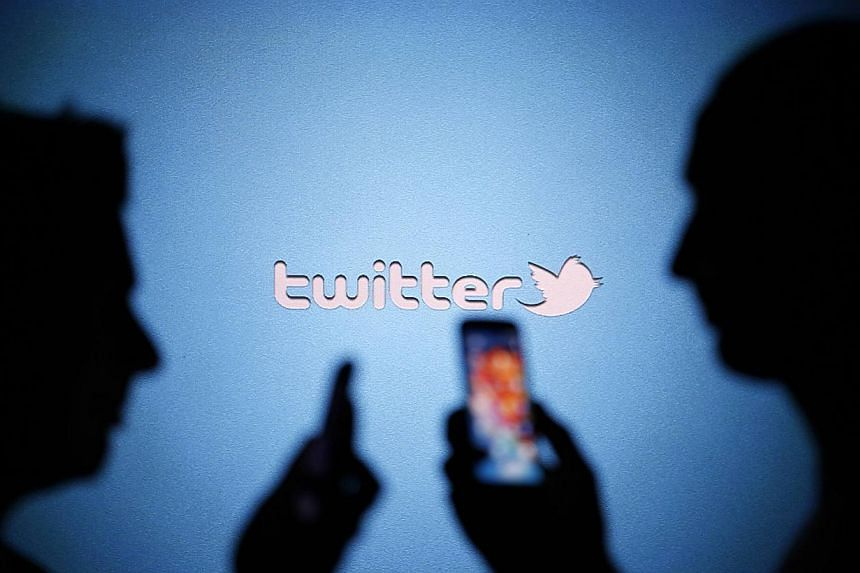 "Men are silhouetted against a video screen with a Twitter logo as they pose with smartphones in this photo illustration taken in Zenica, Bosnia, on Aug 14, 2013. In California on Sept 23, the first-of-its-kind ""eraser button"" law was signed by Govern"