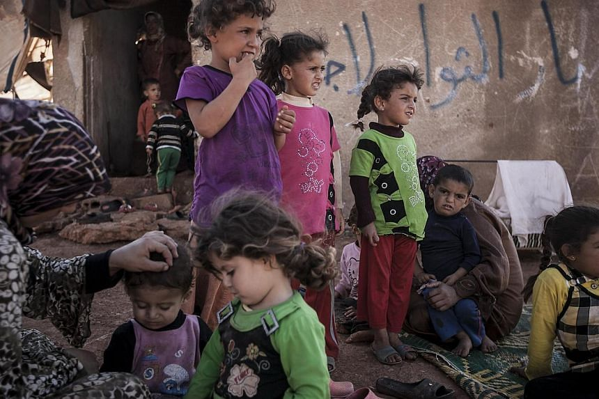 In this Sunday, Sept 22, 2013 photo, Syrian internally displaced families gather at an abandoned land where they have taken shelter after fleeing their village that turned into a battlefield between government forces and Free Syrian Army fighters in