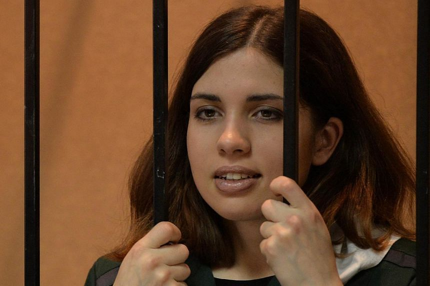 """A picture taken on April 26, 2013, shows one of the jailed members of the all-girl punk band """"Pussy Riot,"""" Nadezhda Tolokonnikova, standing in the defendant's cage in a court in the town of Zubova Polyana, in the Republic of Mordovia.&nbs"""