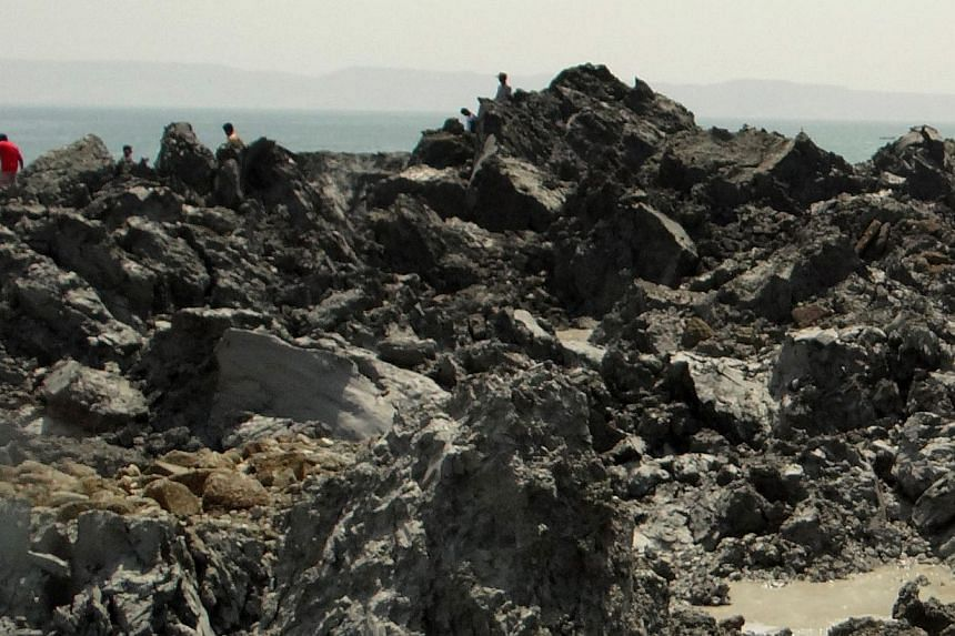 In this photo released by the Pakistani Government, Pakistani men walk on an island that appeared 2km off the coastline of Gwadar on Wednesday, Sept 25, 2013, after an earthquake the day before.-- PHOTO:AFP /PAKISTANI GOVERNMENT