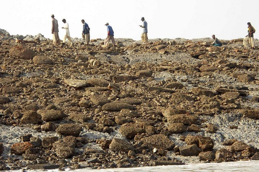 People walk on an island that rose from the sea following an earthquake, off Pakistan's Gwadar coastline in the Arabian Sea on Wednesday, Sept 25, 2013. -- PHOTO: REUTERS
