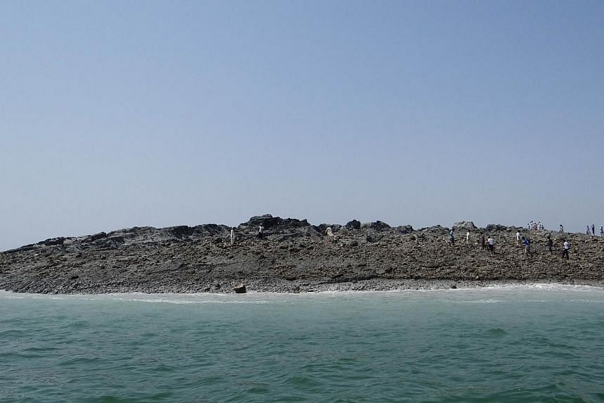 In this photo released by the Pakistani Government, Pakistani men walk on an island that appeared 2km off the coastline of Gwadar on Wednesday, Sept 25, 2013, after an earthquake the day before.A small island created in the Arabian Sea by the h
