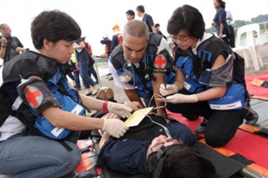 Personnel tending to an injured passenger. -- PHOTO:MARITIME AND PORT AUTHORITY OF SINGAPORE