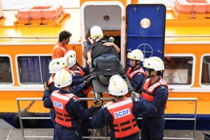 Rescue officers transferring the injured passenger to land. -- PHOTO:MARITIME AND PORT AUTHORITY OF SINGAPORE