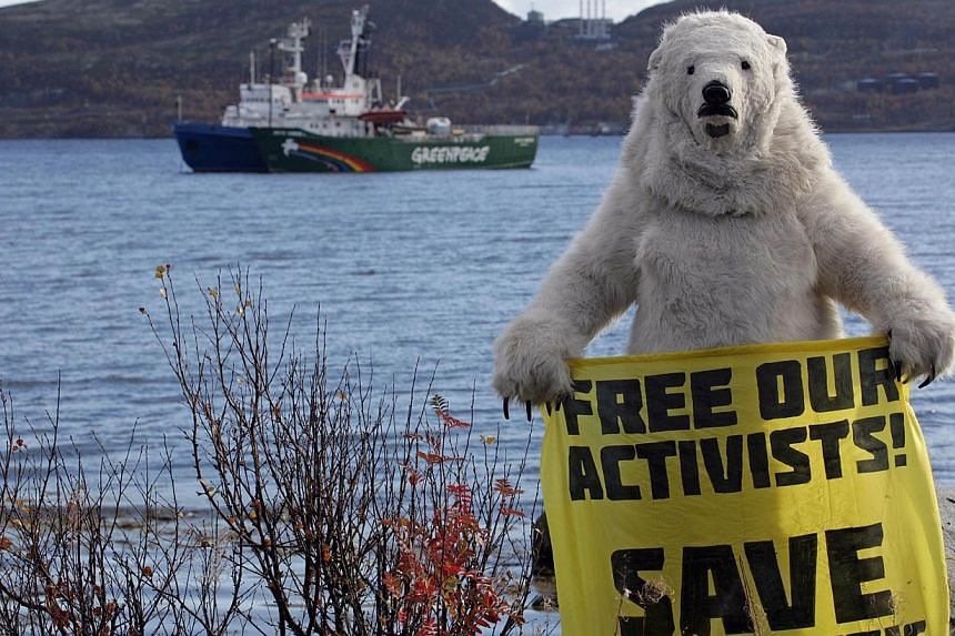 A handout picture taken on Tuesday, Sept 24, 2013, and provided by Greenpeace International shows a Greenpeace activist dressed as a polar bear holding a banner in front of the Arctic Sunrise icebreaker (background) in Kola Bay at the military base S