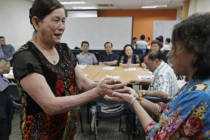 Hawkers Ch'ng Bee Geok (second from left), 66, and Lee Bee Sim, 60, role-playing during yesterday's session. About 70 hawkers from Yu Hua Village Market and Food Centre attended the course.