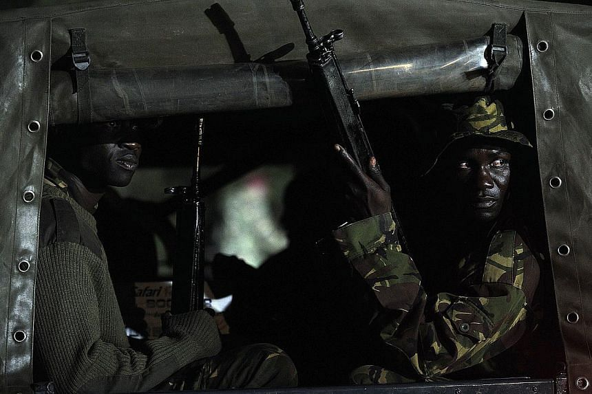 """Kenyan paramilitaries drive towards the Westgate mall on Sept 24, 2013 in Nairobi. Kenyan President Uhuru Kenyatta announced today that the four-day siege by Islamist gunmen of a Nairobi shopping mall was over, with the """"immense"""" loss of 61 civilians"""
