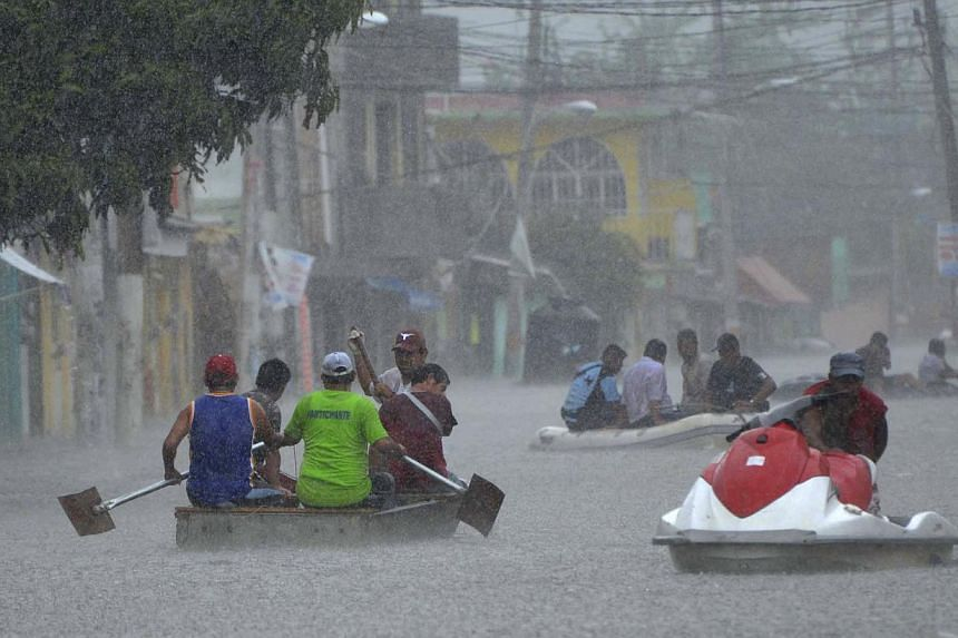 Residents use small boats and jet skis to evacuate and remove their belongings from flooded areas during heavy rain in the town of Titxla de Guerrero, Mexico, on Tuesday, Sept 24, 2013. The death toll from twin storms that battered Mexico has risen t