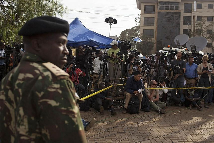 A security officer stands guard as members of the media wait for a news conference by Kenyan government officials, near the Westgate shopping mall in Nairobi September 25, 2013.Kenyan and foreign forensics teams scoured the wreckage of a Nairob