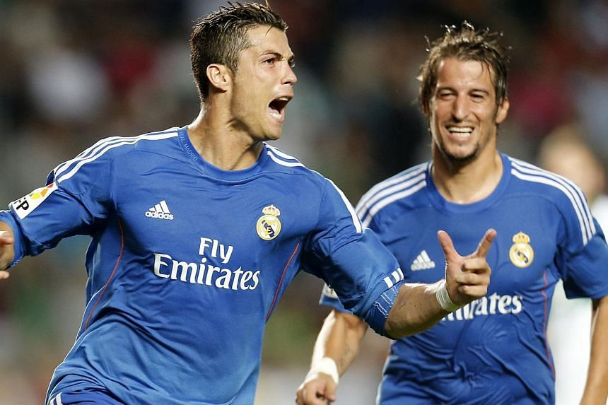 Real Madrid's Portuguese forward Cristiano Ronaldo celebrates after scoring his second goal during the Spanish league football match Elche vs Real Madrid at the Manuel Martines Valero Stadium in Elche on Sept 25, 2013. A dubious injury time Cristiano
