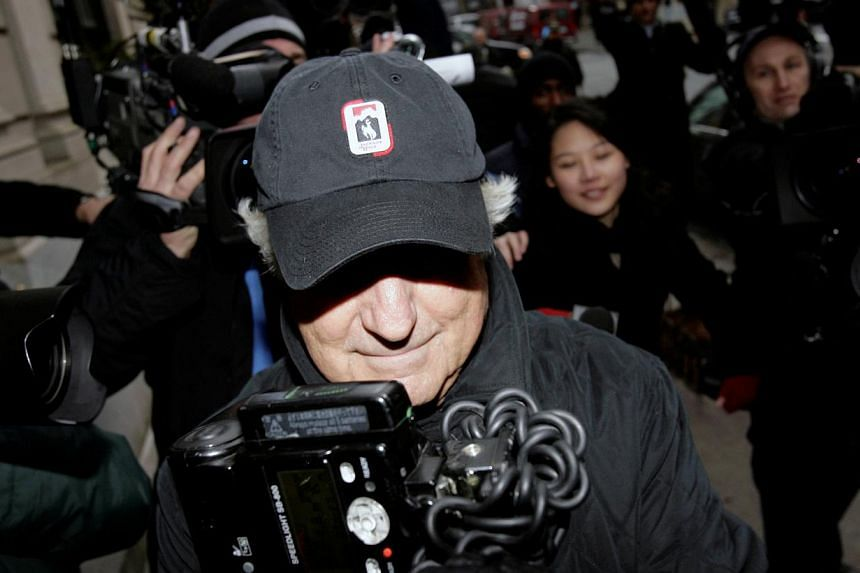 Bernard Madoff enters his house through a crowd of cameras in New York on Wednesday, Dec 17, 2008. A former accountant for Bernard Madoff was arrested on Thursday, Sept 26, 2013, nearly five years after the imprisoned swindler's huge Ponzi schem