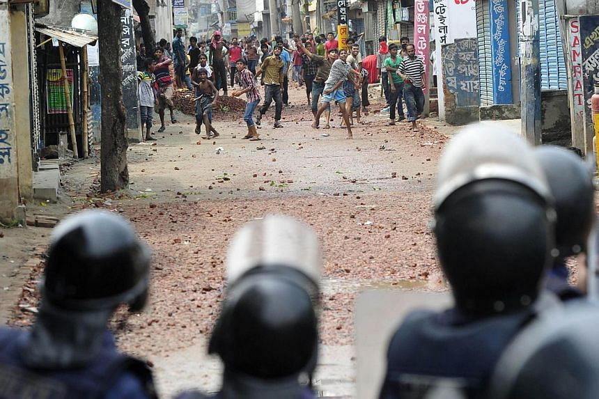 Bangladeshi police officials stand in a line as striking garment workers throw stones during a protest in Narayanganj on Sept 26, 2013. Most Bangladesh garment factories reopened on Thursday, Sept 26, 2013, after five days of violent protests, follow