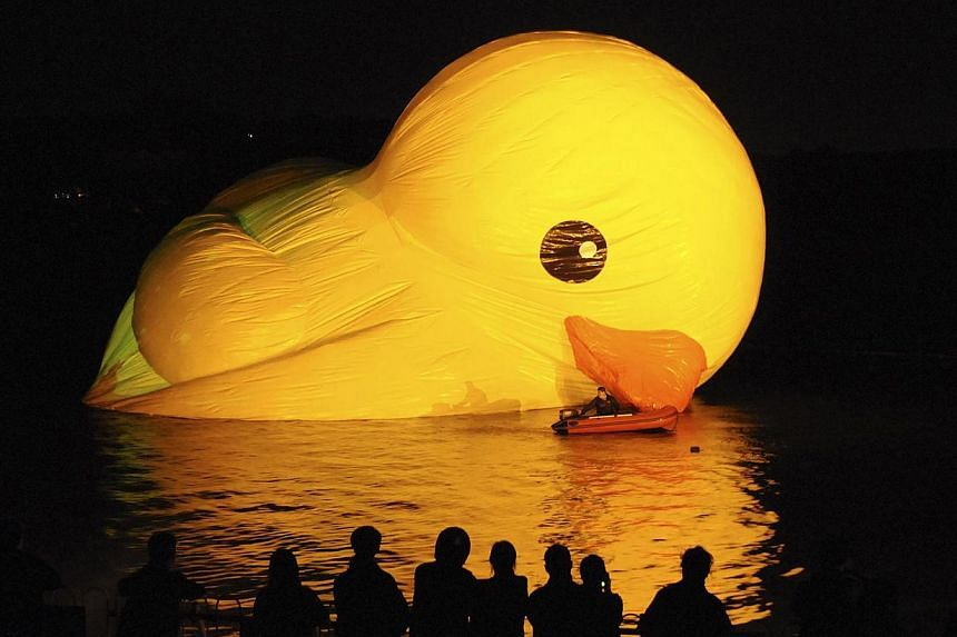 People observe as a Rubber Duck by Dutch conceptual artist Florentijn Hofman is being inflated on a lake at the Summer Palace in Beijing on Wednesday, Sept 25, 2013. -- PHOTO: REUTERS