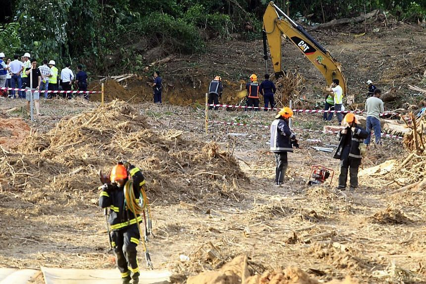 Singapore Civil Defence Force officers working to free Mr Jayaraman, who was trapped in his excavator when the Albizia toppled on Sunday. Workers said he had been trying to fell the tree by loosening the soil at its base.