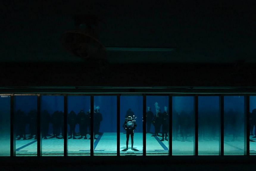 The 73 men from the Naval Diving Unit standing at attention on the floor of a swimming pool during their passing out parade last week. This is the first time the parade has been held underwater in Singapore.