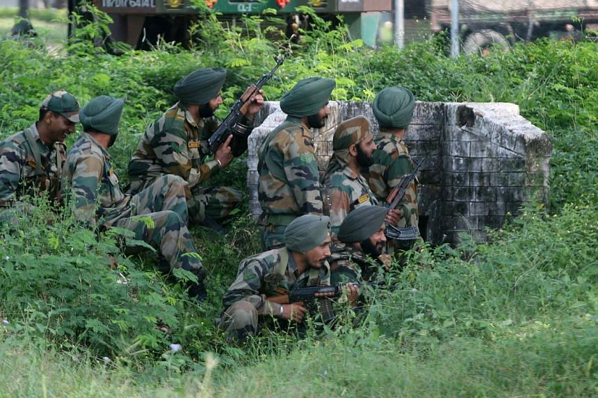 Indian army soldiers gather behind a small wall during an attack by militants on an army camp at Mesar in Samba District, some 20km south-east of Jammu on Thursday, Sept 26, 2013.A group of militants who attacked a police station and army camp