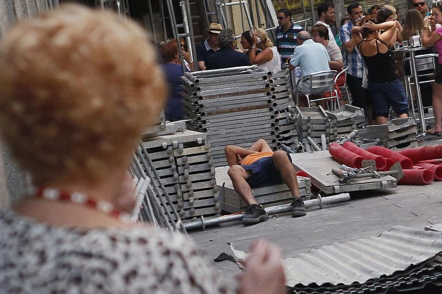 A worker (centre) takes a nap beside a fast food restaurant on July 3, 2012 in Madrid, Spain. Spanish lawmakers proposed switching the country to a different time zone, jumping back an hour to make eating and sleeping habits more regular and workers