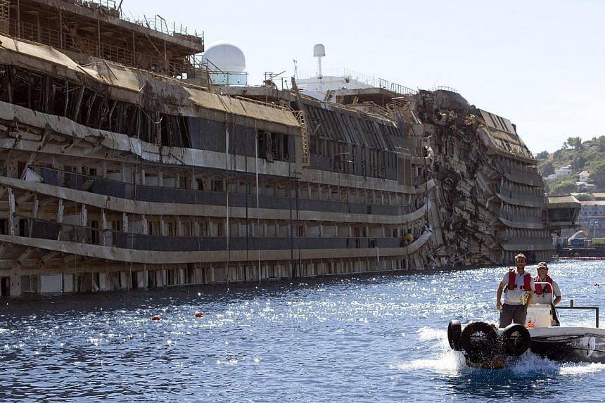 People take a small boat past the damaged side of he Costa Concordia on the Tuscan Island of Giglio, Italy, Wednesday, Sept 18, 2013. Italian divers looking for two bodies missing from last year's Costa Concordia cruise ship disaster which claimed 32