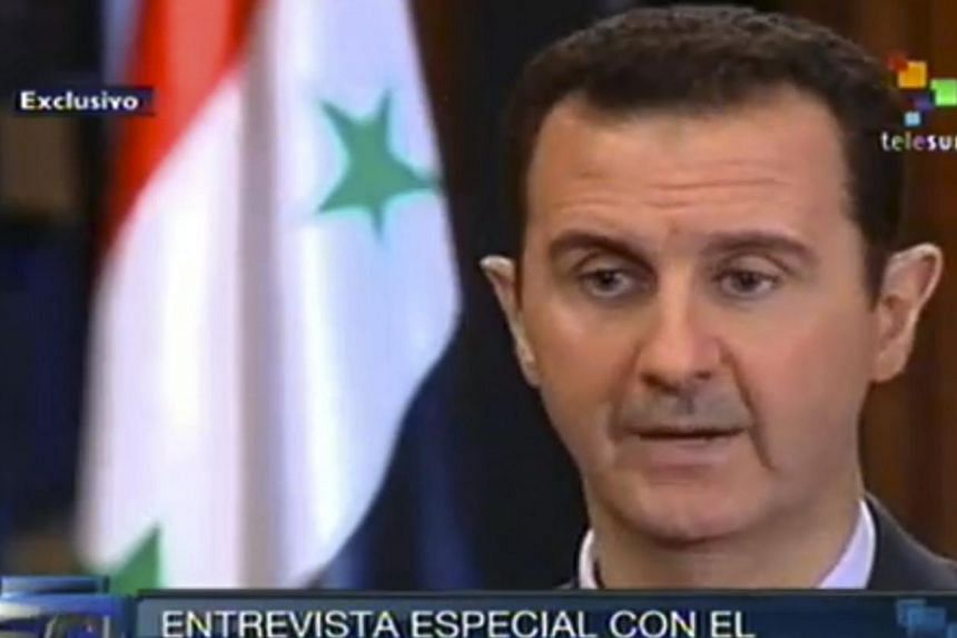 In this frame grab taken from online video broadcast on Telesur television on Wednesday, Sept 25, 2013, Syria's President Bashar al-Assad speaks during an interview with a Telesur reporter in Damascus, Syria.Syria is committed to the convention