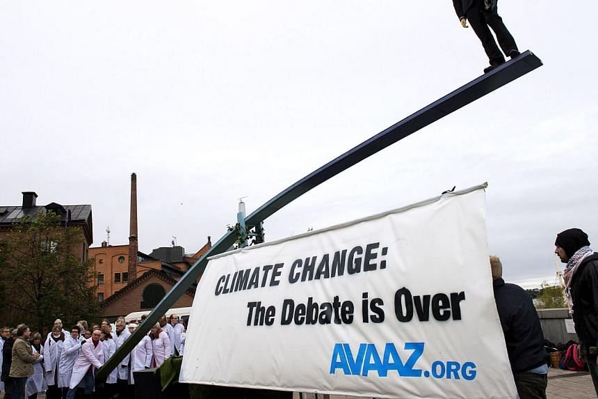 Activists gather outside the the United Nation's Intergovernmental Panel on Climate Change (IPCC) dressed as scientists in lab coats on one side of a giant 12 meter seesaw on Sept 27, 2013 in Stockholm. Leading climate scientists said on Friday Sept
