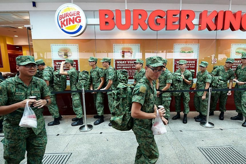 Soldiers walking past a queue for Whopper burgers at a Burger King outlet in White Sands shopping centre in Pasir Ris on Friday, Sept 27, 2013.Burger King gave out 1,000 of its Whopper burgers to soldiers on Friday as a show of appreciation for