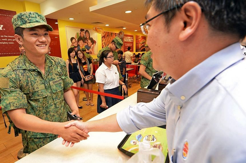 Recruit Zhou Yi Run (left), 21, is congratulated by Wong Shyang Jiuu, general manager for Burger King Singapore, for being the first to receive a free Whopper burger at its White Sands outlet in Pasir Ris on Friday, Sept 27, 2013. He had waited in li