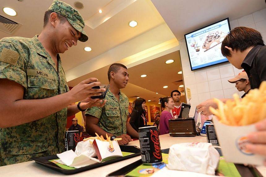 Recruits Melvin Thomas (left) and Shalihin Rahmat, both 19, receiving free Whopper burgers at the Burger King outletin White Sands in Pasir Ris on Friday, Sept 27, 2013.-- ST PHOTO: RAJ NADARAJAN