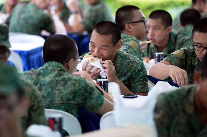 Soldiers tucking into Whopper burgers at the Burger King outlet in White Sands in Pasir Ris on Friday, Sept 27, 2013.-- ST PHOTO: RAJ NADARAJAN
