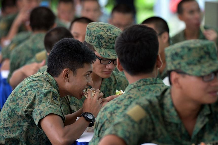 Soldiers tucking into Whopper burgers at the Burger King outlet in White Sands in Pasir Rison Friday, Sept 27, 2013.-- ST PHOTO: RAJ NADARAJAN
