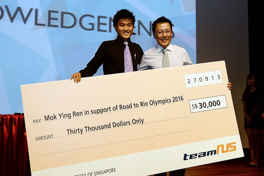 Singapore's top marathoner Mok Ying Ren (left) receiving a cheque from National University of Singapore's Dean of Students, Associate Professor Tan Teck Koon. Mok's dream of competing at the 2016 Olympic Games in Rio de Janeiro was handed a $30,000 b