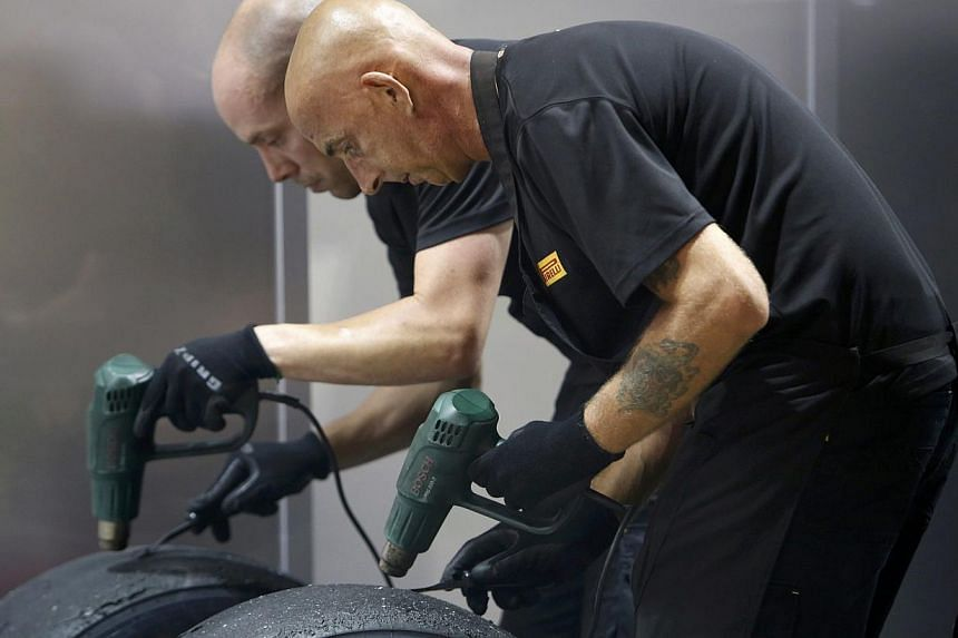 Members of the Pirelli crew scrape tyres to clean them after the second practice session of the Singapore F1 Grand Prix at the Marina Bay street circuit in Singapore Sept 20, 2013. Pirelli can continue as Formula One's sole tyre supplier next season,