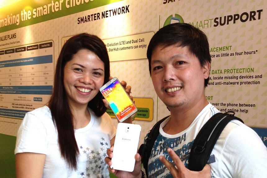 Ms Marianne Judaya (left), 32, and Mr Duke Jason Regular, 37, were the first two StarHub customers to get their Samsung Galaxy Note 3 smartphone. -- PHOTO: STARHUB