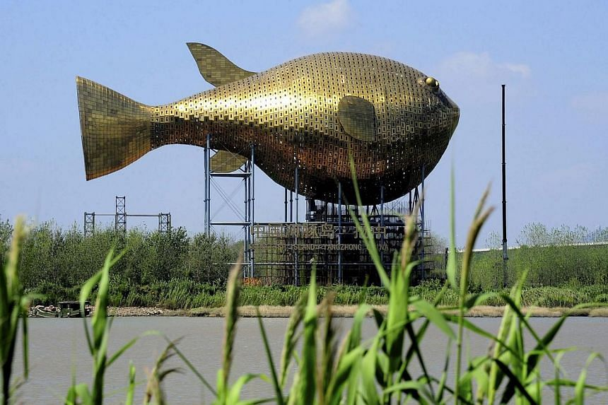 A viewing tower in the shape of a giant copper puffer fish is seen under construction on the banks of a river in Yangzhong county, Jiangsu province, on Sept 21, 2013. Thetower has raised an online huff about the latest in a series of bizarre an