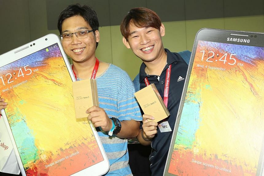 Aesel James (left) and Gedeon Goh are the first two customers in the SingTel queue. -- PHOTO: SINGTEL