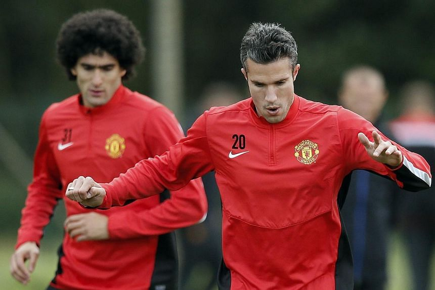 Manchester United's Robin van Persie (right) and Marouane Fellaini warm up during a training session at the club's Carrington training complex in Manchester on Sept 16, 2013. Van Persie has recovered from a groin strain and could feature in Saturday'