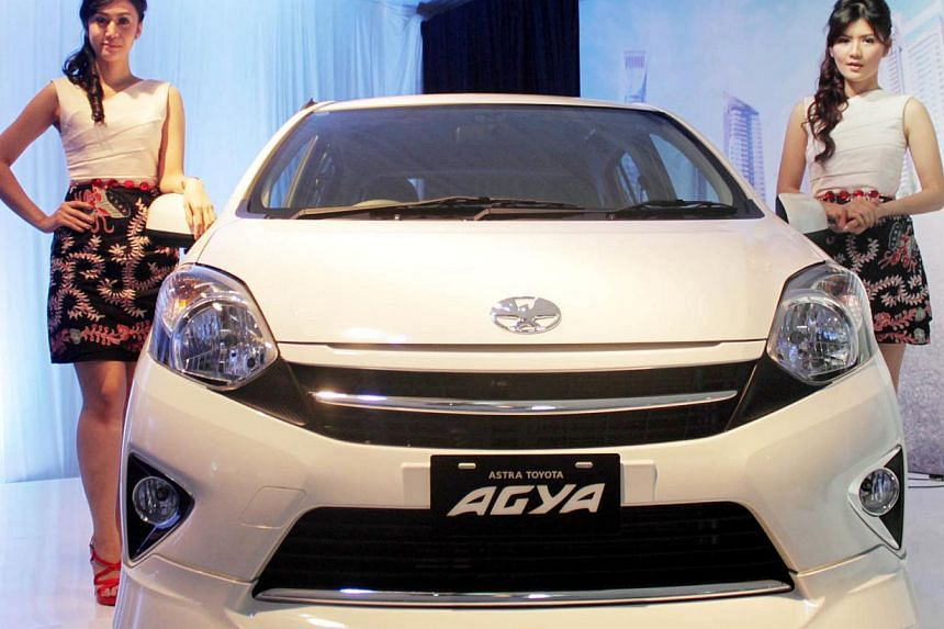 Two models pose by Toyota Astra Motor's Agya car during the launching event on Sept 9. A new Agya hatchback costs 76.5 million rupiah (S$8,400), thanks to government tax breaks. By contrast, a Toyota Hilux pick-up starts from 158 million rupiah