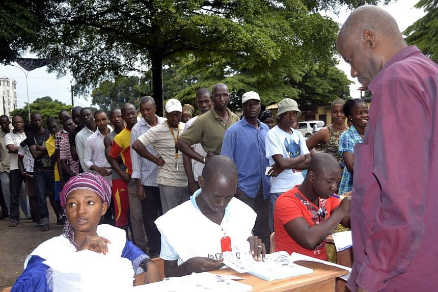 Voters queue at a polling station in Conakry on Saturday, Sept 28, 2013, in the first parliamentary elections in the troubled west African nation for more than a decade, after months of delays and a campaign plagued by deadly unrest.Guineans vo