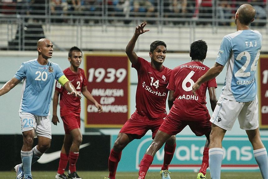 LionsXII player Madhu Mohana (No. 6) celebrates with teammate Hariss Harun (No. 14) after heading in the first and only goal ofthe Malaysia Cup quarter-final match against Malaysian club ATM at the Jalan Besar Stadium on Saturday, Sept 28, 2013