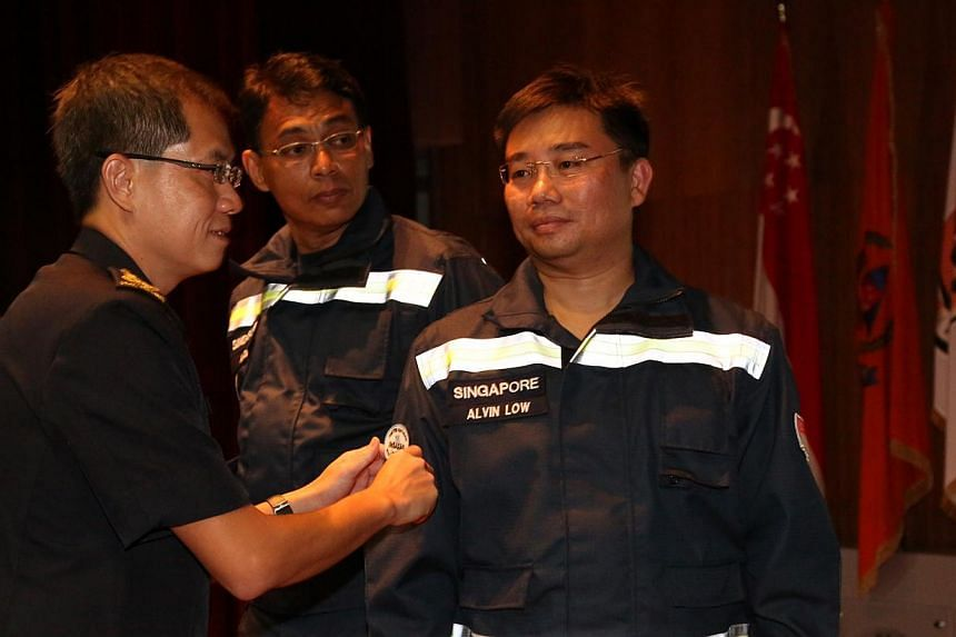 Commissioner Eric Yap places the Heavy USAR Team Badge on NSman Lieutenant-Colonel Alvin Low. -- PHOTO: SCDF