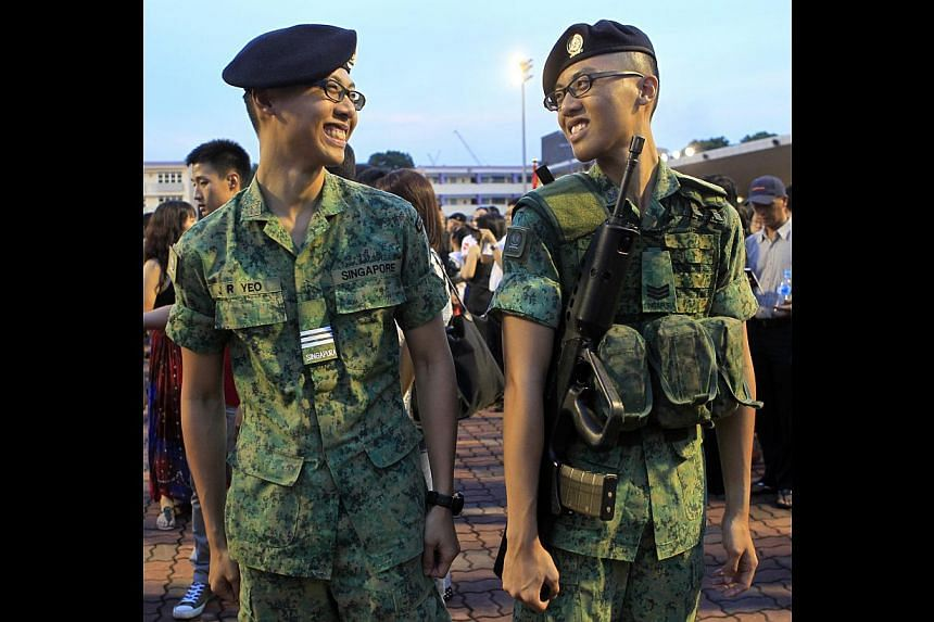 3SG Jin Rui (right) was all smiles yesterday after having his insignia put on by his twin brother, OCT Jin Run (left). In all, 995 specialist cadets received their new ranks at the graduation parade at Pasir Laba camp.