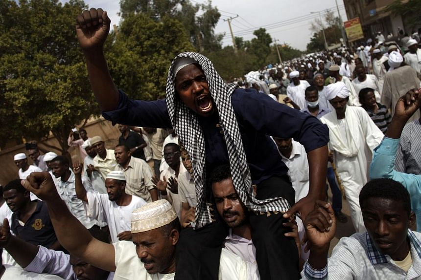 Sudanese anti-government protesters chant slogans after the Friday noon prayer in the Omdurman district of northern Khartoum, Sudan on Friday, Sept 27, 2013.Thousands of demonstrators called Sudanese President Omar al-Bashir a killer on Saturda