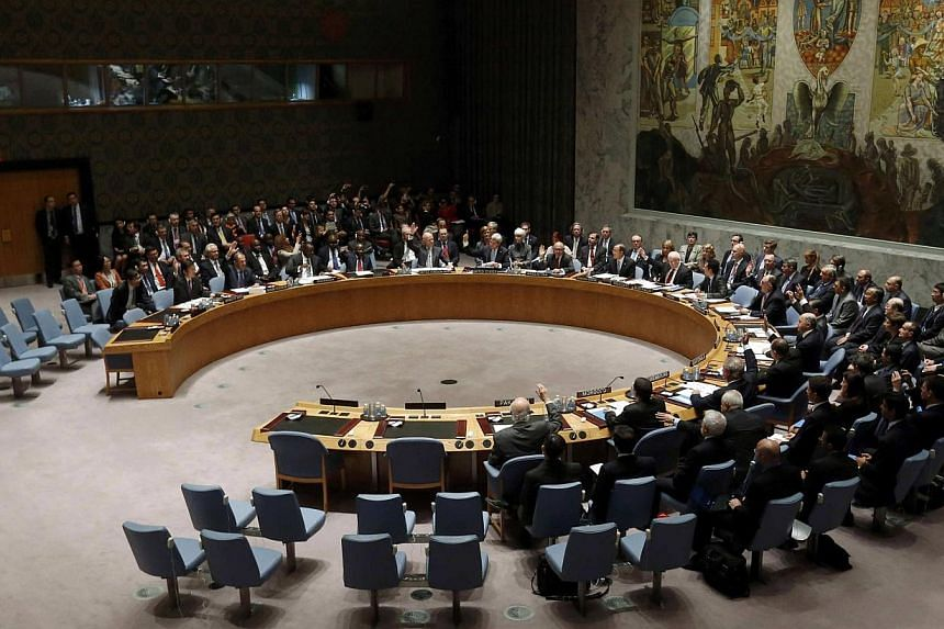 Members of the United Nations Security Council raise their hands as they vote unanimously to approve a resolution eradicating Syria's chemical arsenal during a Security Council meeting during the 68th United Nations General Assembly in New York on Fr
