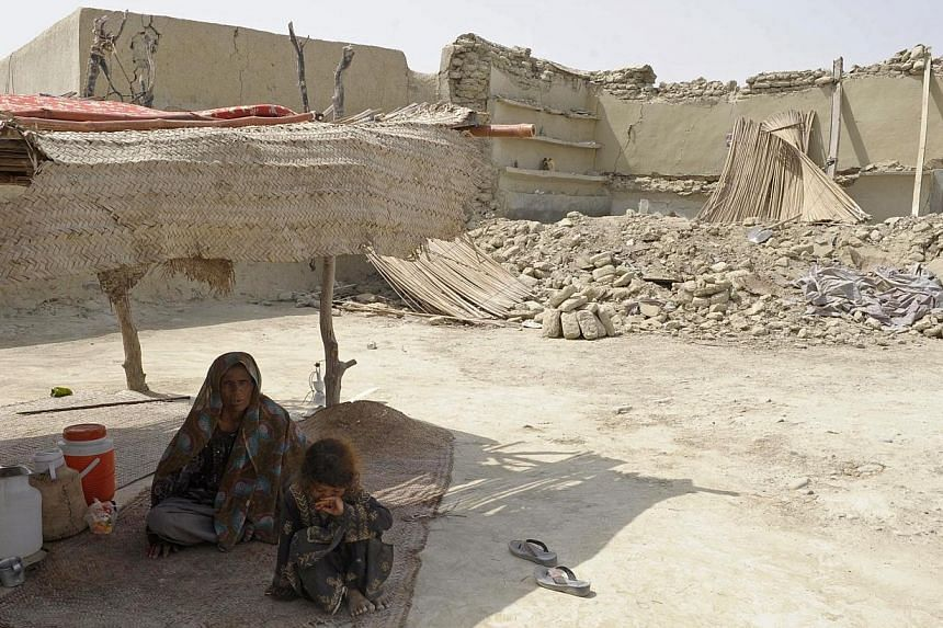 A Pakistani earthquake survivor sits under a makeshift shelter in the devastated district of Awaran on Wednesday, Sept 25, 2013. A powerful 6.8-magnitude earthquake hit south-west Pakistan on Saturday, killing at least 12 people in a region already d